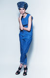 Fashionable woman in denim jumpsuit and hat Stock Photography