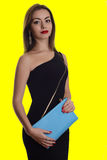 Fashionable woman with a dlue bag in her hands and black evening dress Stock Images