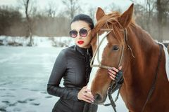 Fashionable woman is holding a horse stock photos