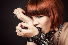 Fashionable woman gnaws leather handcuffs Stock Images