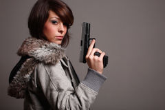 Fashionable woman with gun. A young fashionable woman holding a pistol Stock Photography