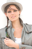 Fashionable woman in hat. Portrait of an attractive fashionable young woman with plaited hair wearing a trilby style hat and casual khaki jacket Stock Image