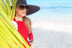 Fashionable woman hiding behind palm leaf on the beach Stock Photos