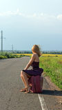 Fashionable woman hitchhiking at roadside. Fashionable woman in a sundress and stilettoes facing away from the camera hitchhiking at the roadside in the Royalty Free Stock Images
