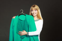 Fashionable woman holding green coat Royalty Free Stock Image
