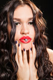 Fashionable woman holding a jewel in lips Royalty Free Stock Photography