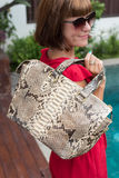 Fashionable woman holding leather snakeskin python bag. Elegant outfit. Close up of purse in hands of stylish lady Stock Image