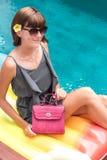 Fashionable woman holding luxury stylish snakeskin python bag. Elegant outfit. Close up of purse in hands of stylish Royalty Free Stock Image