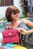 Fashionable woman holding luxury stylish snakeskin python bag. Elegant outfit. Close up of purse in hands of stylish Stock Images