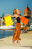 Fashionable woman jumping with shopping bags Stock Photos