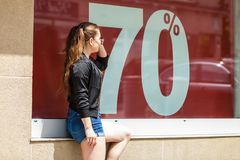 Woman standing next to sale sign. Fashionable woman looking at 70 percentage sale marketing sign. Female wants to buy something at shop Stock Images