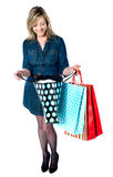 Fashionable woman looking into shopping bags Stock Photo