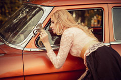 Fashionable woman looks in the side mirror retro car Royalty Free Stock Photo