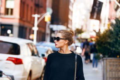 Fashionable woman model walking on New York City street wearing sunglasses and black sweater. Stock Images