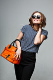 Fashionable woman with an orange bag and Large Round Sunglasses. Stock Image