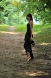 Fashionable woman outdoors. Fashionable young woman wearing dress walking barefoot in countryside, wood in background Royalty Free Stock Images