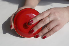 Fashionable woman painted red nail polish, hand, two hands holding a red tea cup cover. Fashionable woman is full of red nail polish on fingers, only two hands royalty free stock photos