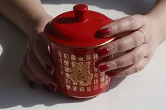 Fashionable woman painted red nail polish, hand, two hands holding a red tea cups. Fashionable woman is full of red nail polish on fingers, hands holding a red royalty free stock image