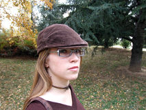 Fashionable woman in park. Portrait of fashionable young woman with hat in autumnal park royalty free stock image