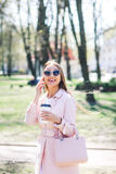 Fashionable woman with phone and cofee in the city. Fashion woman in a sunglasses and pink jacket outdoor Royalty Free Stock Photo