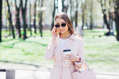 Fashionable woman with phone and cofee in the city. Fashion woman in a sunglasses and pink jacket outdoor Stock Images