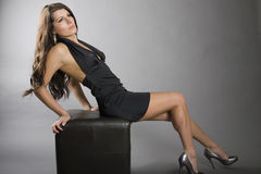 Fashionable woman posing. Side view of fashionable young woman wearing black dress reclining on seat, studio background Stock Photography