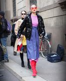 MILAN - FEBRUARY 24, 2018: Fashionable woman posing for photographers in the street after ERMANNO SCERVINO fashion show, royalty free stock images