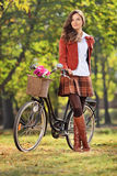Fashionable woman posing with her bicycle in park Royalty Free Stock Image