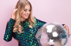 Fashionable woman posing with silver disco ball. Beautiful blonde woman in fashionable party dress. Glamour style beauty portrait. Girl posing on pastel pink Royalty Free Stock Photos