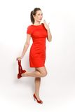 Fashionable woman in red. Beautiful brunette in red dress with red shoes heel is being photographed in the studio on a white background, and she undresses red Royalty Free Stock Photo