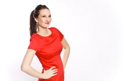 Fashionable woman in red. Beautiful brunette in red dress is being photographed in the studio on a white background Stock Photography