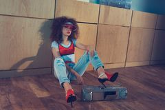 Fashionable woman with boombox sitting on floor. Fashionable woman in red cap and high heels sitting near boombox on floor royalty free stock image