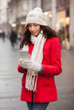 Fashionable woman in red coat and wool cap and gloves with smartphone in han Stock Photos