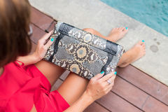 Fashionable woman in red dress holding leather snakeskin python bag. Elegant outfit. Close up of purse in hands of Stock Image