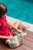 Fashionable woman in red dress holding leather snakeskin python bag. Elegant outfit. Close up of purse in hands of Stock Images