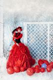 Fashionable woman in red lavish dress posing. Fashionable woman in red lavish dress posing under falling snow Stock Photography