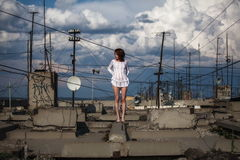 Fashionable woman on roof. Fashionable woman in short white dress stood on urban roof with aerials in city Royalty Free Stock Image