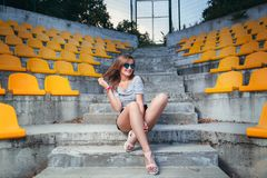 Fashionable woman with round glasses. Sitting on the steps of the stadium outdoor Stock Image