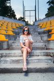 Fashionable woman with round glasses. Sitting on the steps of the stadium outdoor Royalty Free Stock Photography