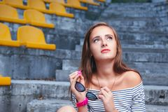 Fashionable woman with round glasses sitting on the steps. Of the stadium Royalty Free Stock Images