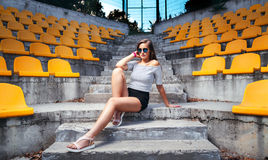 Fashionable woman with round glasses sitting on the steps. Of the stadium royalty free stock photography