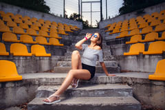 Fashionable woman with round glasses sitting on the steps. Of the stadium stock images