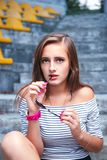 Fashionable woman with round glasses sitting on the steps royalty free stock images