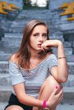 Fashionable woman with round glasses sitting on the steps. Of the stadium Stock Photo