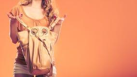 Fashionable woman searching through handbag. Stock Image