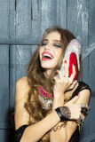 Fashionable woman with shoe. Attractive glamour young fashionable girl with long curly hair bright makeup and costume jewellery of necklace rings and earrings Stock Photography