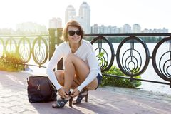 Fashionable woman in shoes and with a bag. On the background of the city and water, in sunglasses at sunset Royalty Free Stock Image