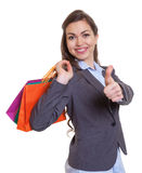 Fashionable woman with shopping bags showing thumb up Royalty Free Stock Images