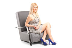 Fashionable woman sitting in a modern armchair Royalty Free Stock Photos