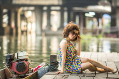 Fashionable woman sitting on a wooden river pier. Stock Image